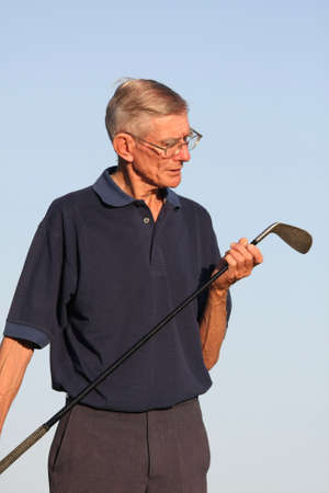 Golfer looking at his iron golf club photo