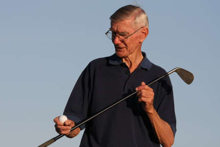 Elderly golfer inspecting his golf ball and club photo