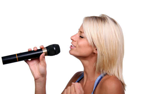 Pretty blond woman singing into a microphone