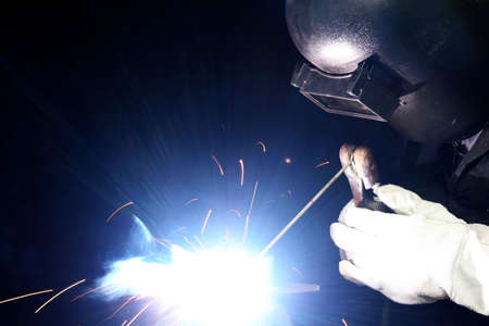 trained: Blue smoke and bright light from a welder busy working