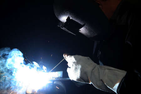 Welder with protective gloves and helmet welding steel