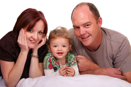 Mother and father with their cute daughter lying between them Stock Photo - 4861894
