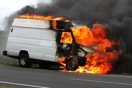 Delivery type vehicle on side of road burning with large flames and smoke
