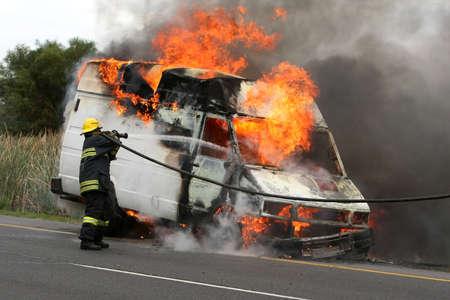pyromaniac: Fireman spraying water into a burning van on a road Stock Photo