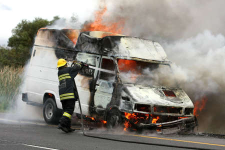 Fireman extinguishing a fire in a burning delivery van Stock Photo