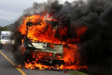 Vehicle ablaze with huge orange flames and black smoke photo