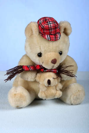playthings: Teddy bear toy dressed with red cap and holding a baby Stock Photo