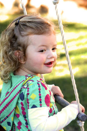 Pretty little girl playing on a rope ladder in her garden Stock Photo - 4955354