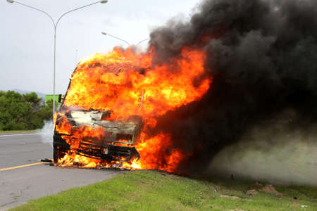 Delivery vehicle burning on the side of the road with huge orange flames photo