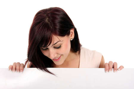 Gorgeous smiling brunette holding a white presentation board and looking down Stock Photo - 5015597