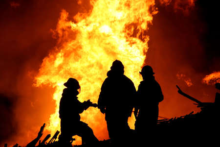 Silhouette of three firemen fighting a huge fire of burning timber Stock Photo