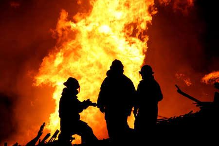 Silhouette von drei Feuerwehrleute im Kampf mit einem riesigen Feuer der brennenden Holz Standard-Bild