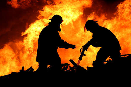 Silhouette of two firemen fighting a huge fire of burning timber