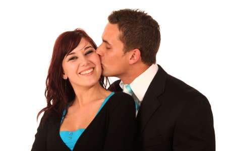cheek to cheek: Handsome man kissing his smiling girlfriend on her cheek Stock Photo
