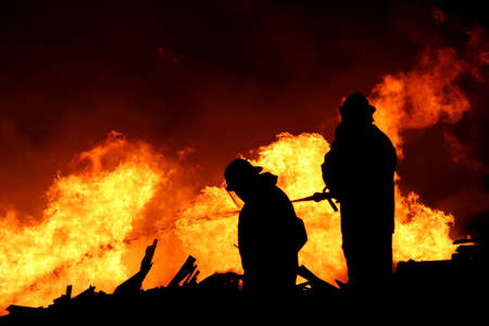 fireman: Silhouette of two firemen fighting a raging fire with huge flames of burning scrap timber