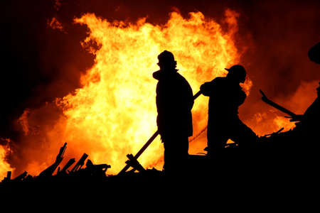 building insurance: Firemen fighting a raging fire with huge flames of burning timber