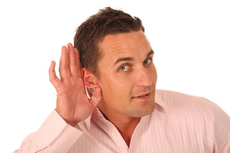 Handsome hard of hearing young man with hand to ear  Stock Photo