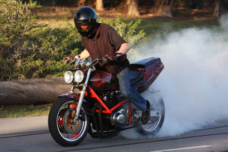 drag: Motorbike rider on custom bike burning back tire and creating smoke