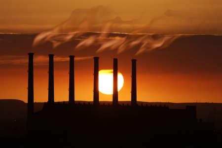 smokestacks: Smoking factory chimneys at sunset adding to global warming Stock Photo