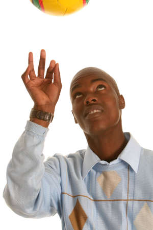 Young African man throwing a soccer ball up photo