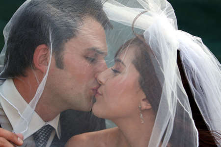 Happy wedding couple kissing under the brides veil photo