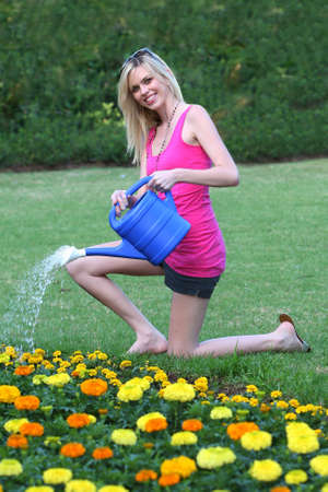 Pretty young lady with lovely smile watering flowers with a watering can photo