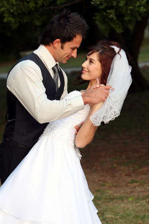 Beautiful wedding couple dancing on the lawn at their reception photo
