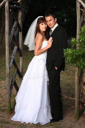 young couple smiling: Handsome wedding couple standing under a wooden arch outdoors