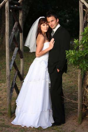 pareja abrazada: Pareja de boda guapo de pie bajo un arco de madera al aire libre  Foto de archivo