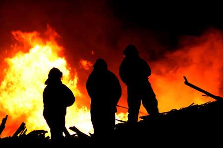пожарный: Три пожарные борются бушует огонь с огромными пламени горящего леса Фото со стока