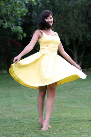 yellow dress: Pretty girl dancing outdoors on green grass