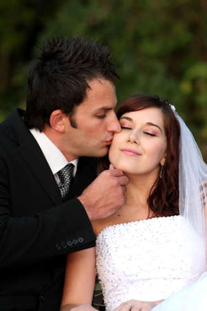 Groom kissing his lovely bride on her cheek on their wedding day photo