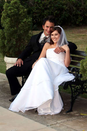 Beautiful smiling young wedding couple sitting together at their garden reception photo