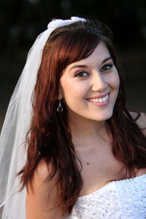 Stunning bride with lovely smile in a beautiful wedding dress photo