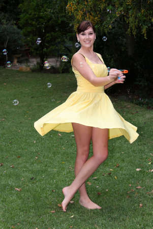 twirls: Gorgeous brunette girl in yellow dress twirling round an blowing soap bubbles