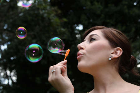 blowing bubbles: Pretty young woman blowing soap bubbles outdoors