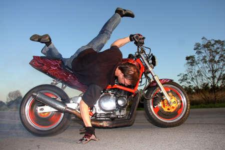 Motorbike rider performing a stunt on his custom motorcycle photo