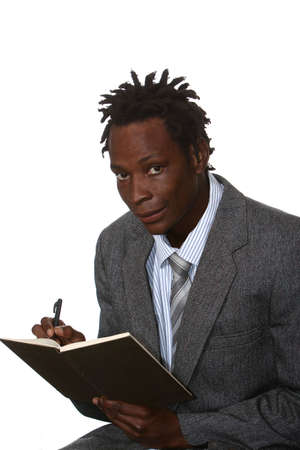 Young African American business man with dreadlocks hairstyle writing in book Stock Photo - 6908019