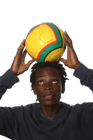 south african: Young South African man with soccer ball on his head