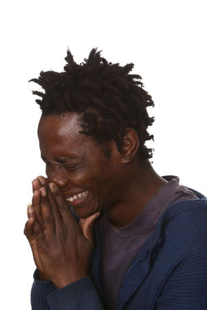 Young African man with hands to nose as he sneezes photo