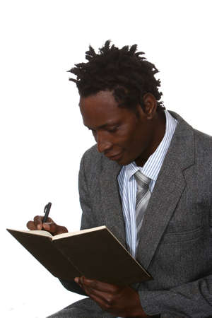 Young African American business man with dreadlocks hairstyle writing in book photo