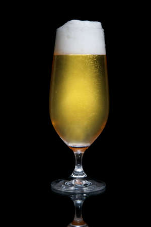 Ice cold beer with frothy head against black background photo