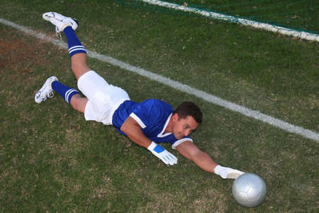 Soccer goal keeper diving to stop the ball from entering the net photo