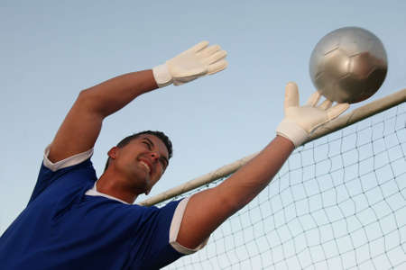 futbol: Soccer goal keeper stretching to save the ball
