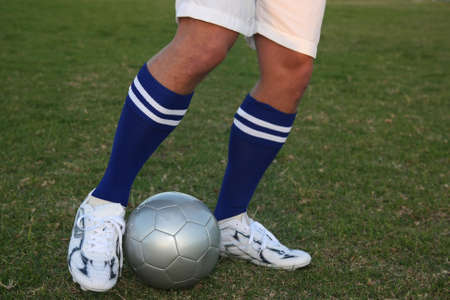 Soccer players legs in position to kick the ball photo