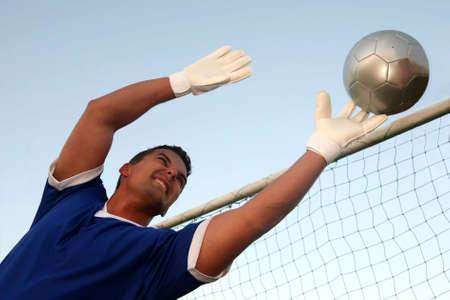 arquero: Portero de f�tbol, que se extiende a parar la bola  Foto de archivo