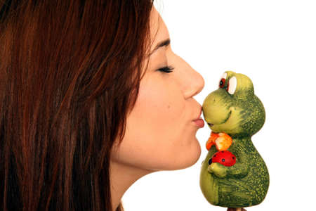 Pretty brunette girl kissing a toy frog photo