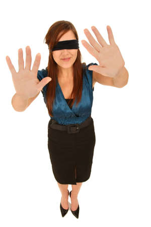 Beautiful brunette girl with blindfold and feeling her way photo