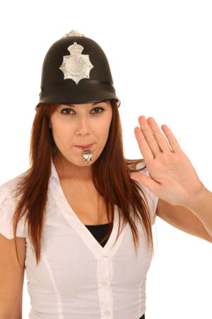 Pretty police woman with hand out and blowing a whistle photo
