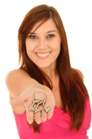 Beautiful smiling real estate woman offering keys - focus on keys